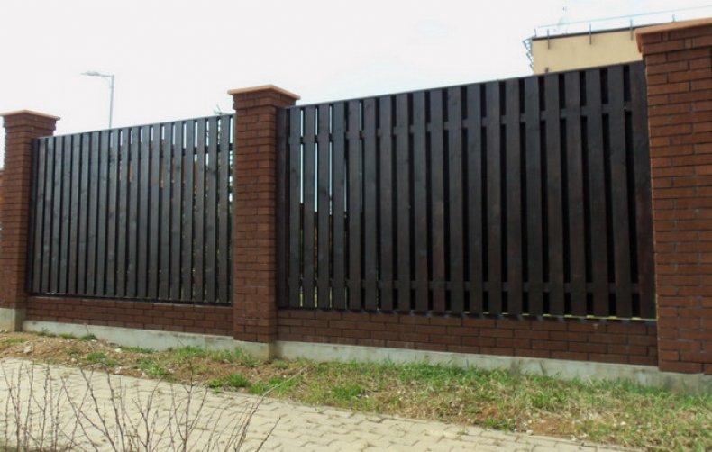 Кирпичный забор с деревянными ставками